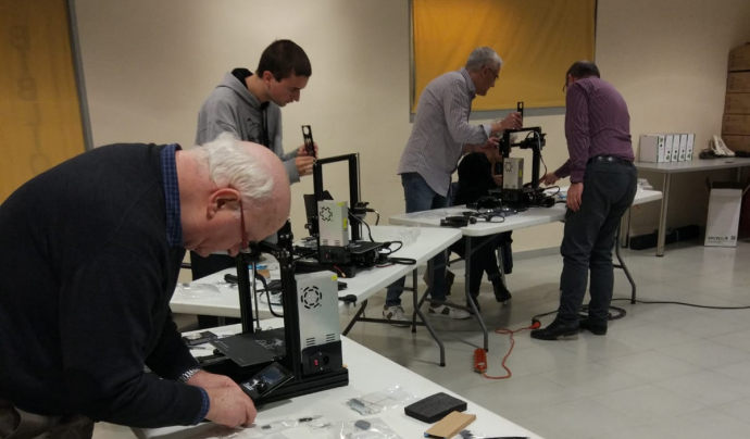 Persones de diferents edats treballant amb impressores 3D
