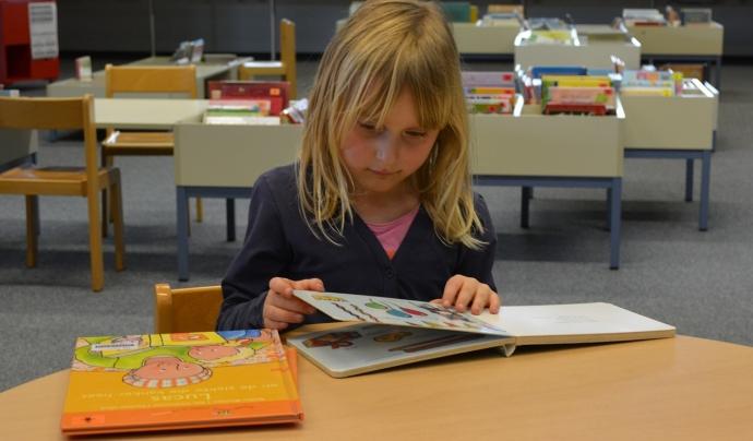 Una nena llegint en una biblioteca