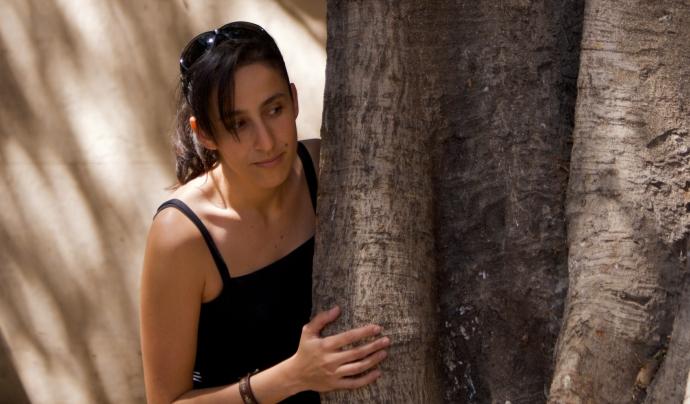 Noia darrere d'un arbre