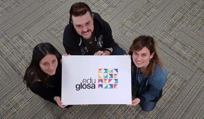 Tres membres d'Eduglosa mostren el logotip del projecte