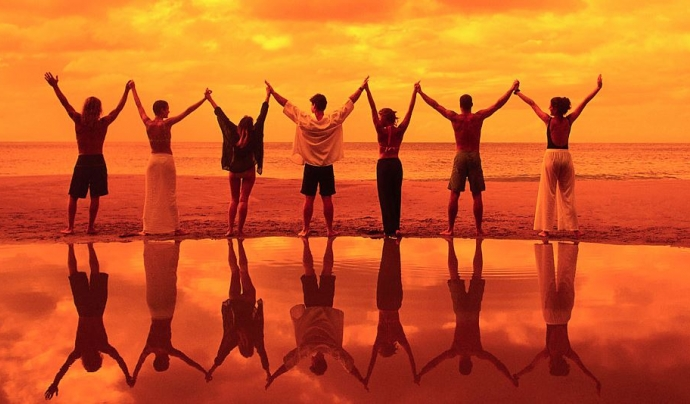Noies i nois amb mans aixecades i agafades davant del mar