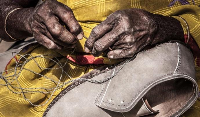 Una treballadora cosint sabates a casa seva. Font: Campanya Roba Neta