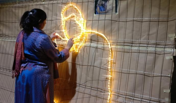 Una dona que treballa en el projecte #RavalKm0 creant els arcs lumínics del Nadal