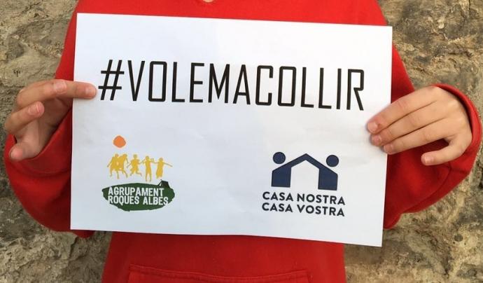 Les mans d'un infant sostenint un cartell fet per l'Agrupament Roques Albes per a donar suport a la manifestació