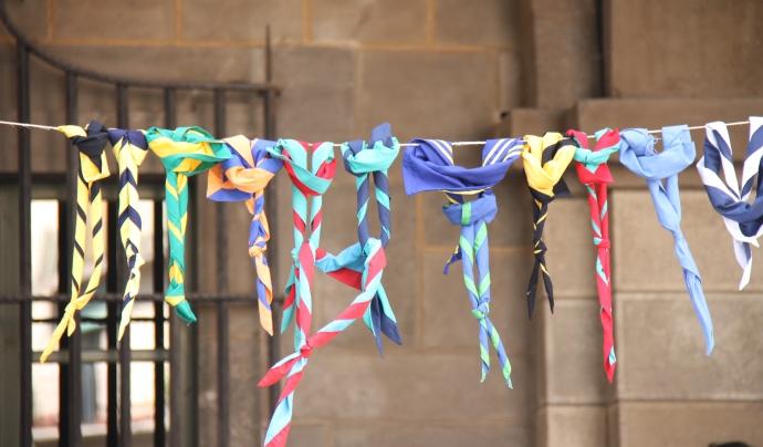 Exposició de fulards d'agrupaments escoltes de Catalunya penjats d'un fil.