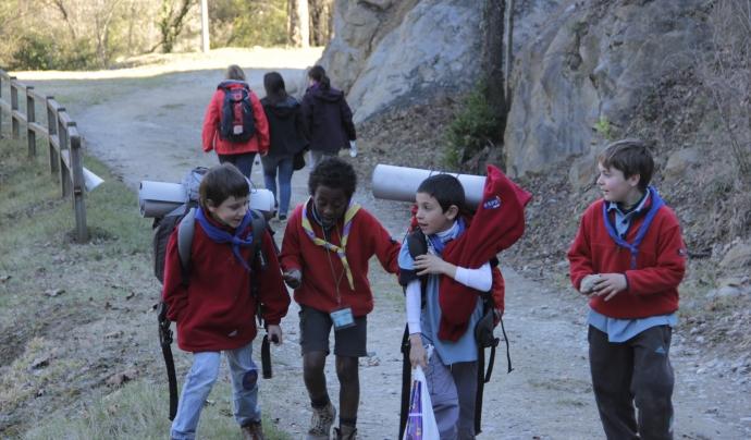 Infants caminant i carregant les motxilles durant una excursió del cau