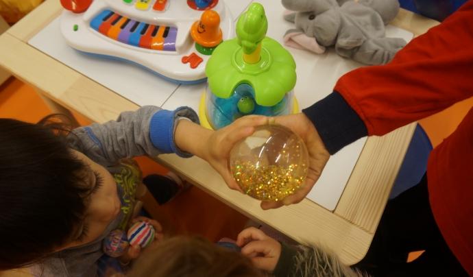 Infants jugant agafant una bola transparent amb les mans