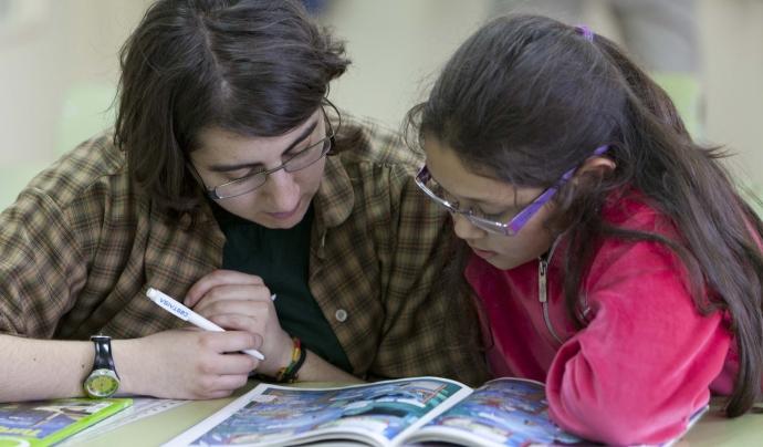 Una voluntària ensenya una nena a llegir