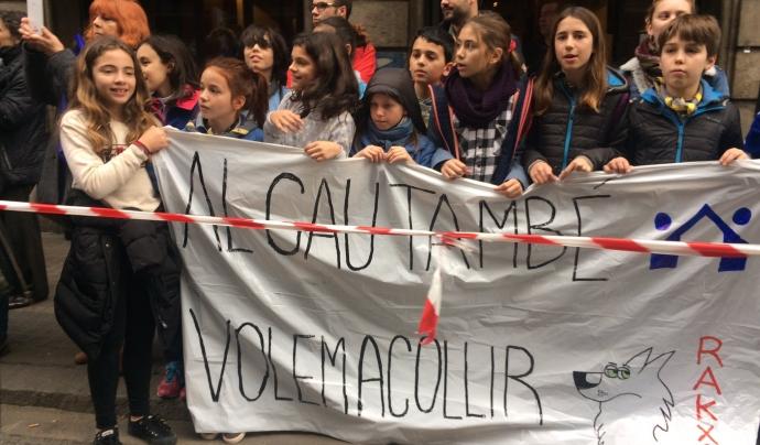 """Un grup d'infants escoltes a la manifestació #VolemAcollir amb una pancarta que diu """"Al cau també volem acollir"""""""