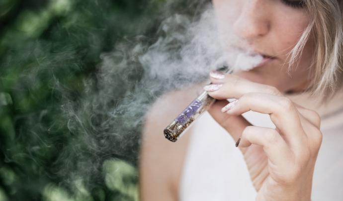 Una dona fuma un cigarret de marihuana.