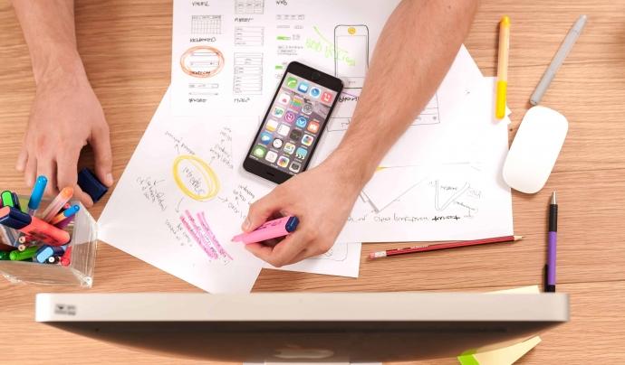 Braós de persona sobre d'una taula plena de papers escrits i un smartphone