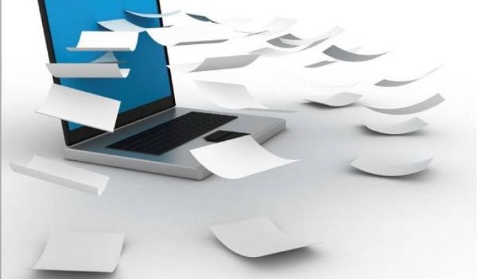 Ordinador amb papers;Font:www.tusimpuestosaldia.com