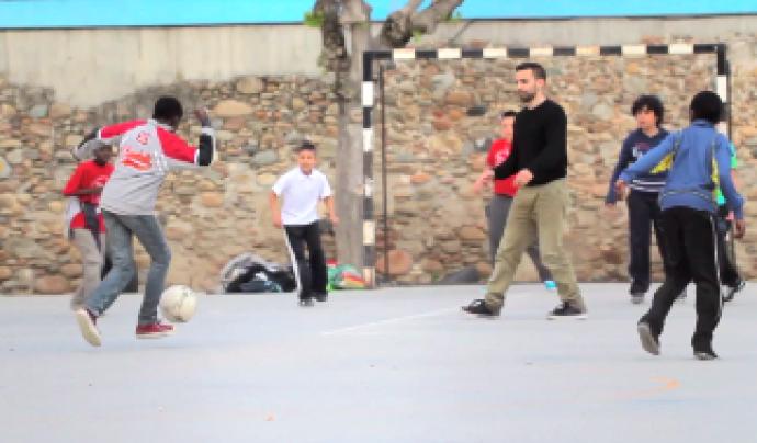 Jove voluntari jugant a futbol amb adolescents en un camp a Salt (Font: OCD de la UdG)