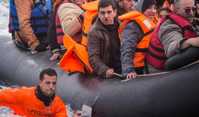 Un membre de Proemaid acompanya un bot inflable ple de persones refugiades