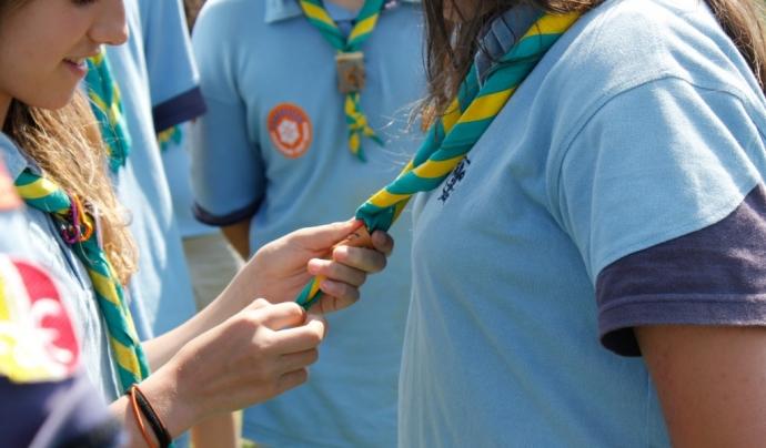 Joves lligant-se el fulard durant la promesa escolta