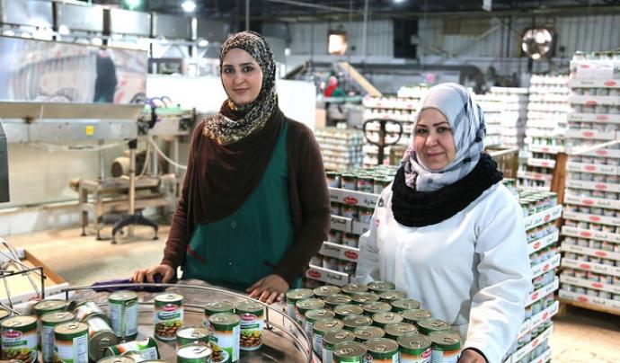 Dues refugiades treballen a una fàbrica d'aliments. Font: Bea Arscott, Flickr