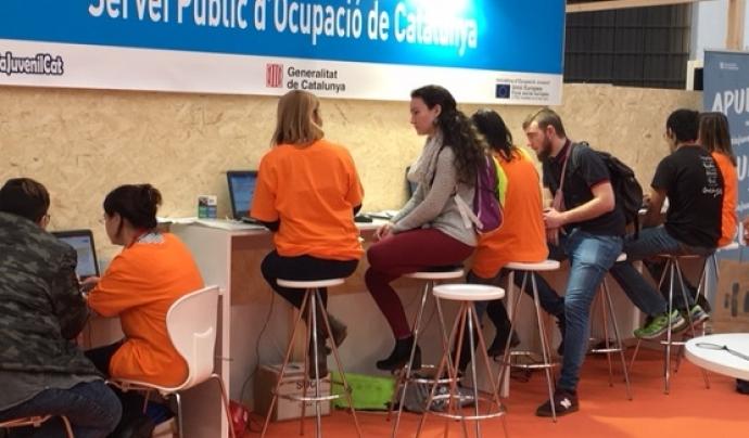 Joves assessorant-se en l'estand del SOC en el primer Saló de l'Ocupació Juvenil