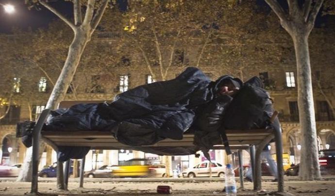 Una persona sense sostre dorm en un banc al costat de la Ciutadella Font: Joan Cortadellas (El Periódico)