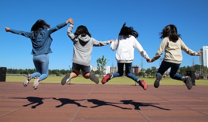 Noies saltant d'esquena
