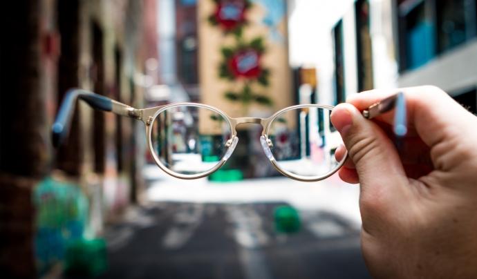 Una persona subjecta unes ulleres al mig del carrer.
