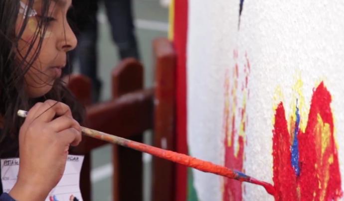 """Una nena participant del projecte """"Vincular x educar"""" pintant dibuixos la paret"""
