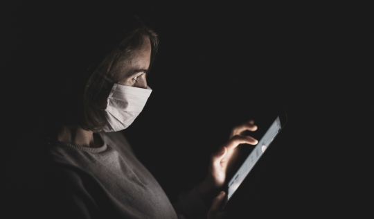 Persona amb mascareta llegit una tauleta Font: Engin Akyurt a Unsplash