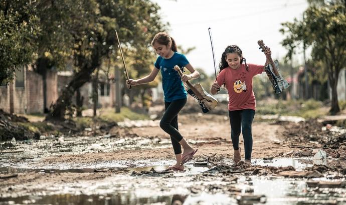 Dues noies membres de l'Orquestra d'Instruments Reciclats de Cateura saltant bassals amb els seus instruments fets amb material reciclat
