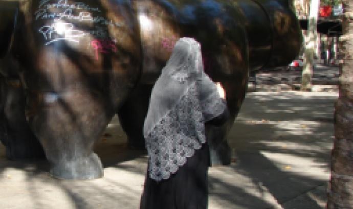 Dona migrada passejant-se per la Rambla del Raval. Font: ECAS