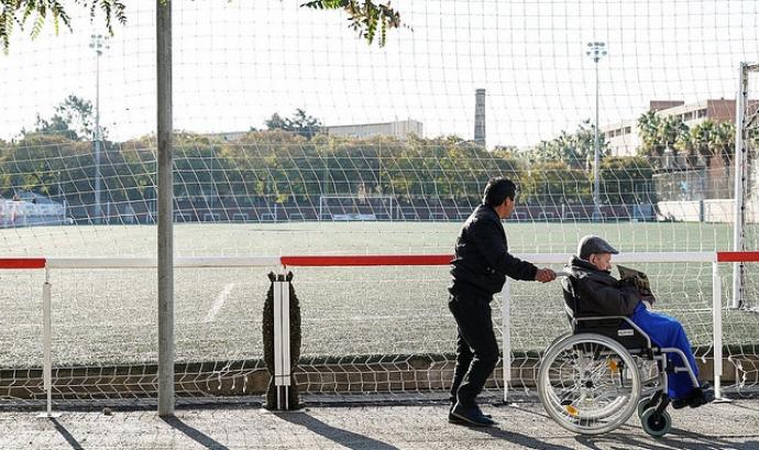 Una persona acompanya a una altra amb cadira de rodes