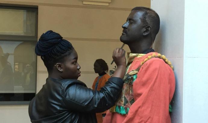 Una noia pintant la cara de negre a un home blanc