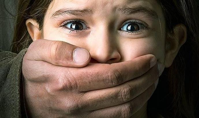 Imatge d'una nena a la que un home li tapa la boca. Font: web abc.es
