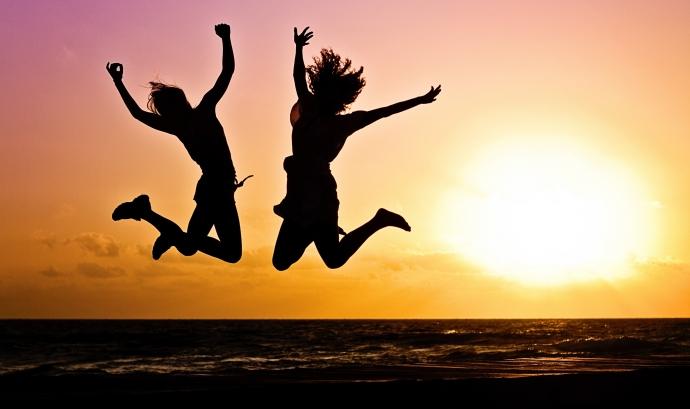 Dues noies salten d'alegria a la platja amb una posta de sol.