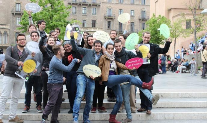 Participants de la 10a Àgora Jove amb cartells tipus bafarada que contenen consignes de participació.