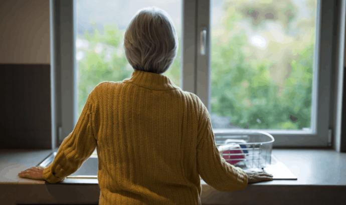 Una persona gran amb Alzheimer observa per la finestra. Font: Fundació Pasqual Maragall