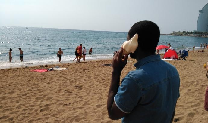 Una persona migrada s'apropa un cargol de mar a l'orella a la platja de Sant Sebastià.