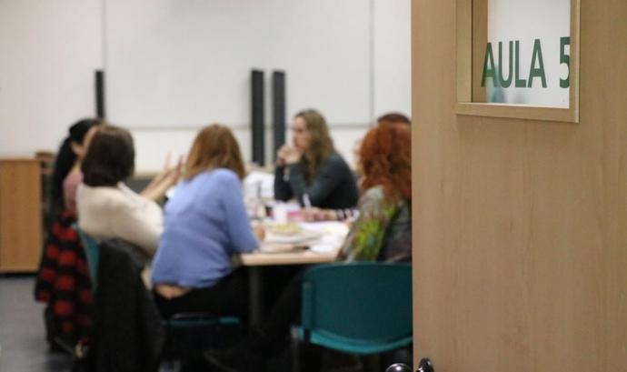 Porta obert a un aula amb dones reunides al voltant d'una taula