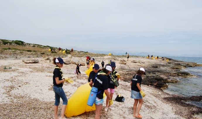 Un grup d'infants escoltes netejant un fragment de costa durant la campanya Clean up the Med