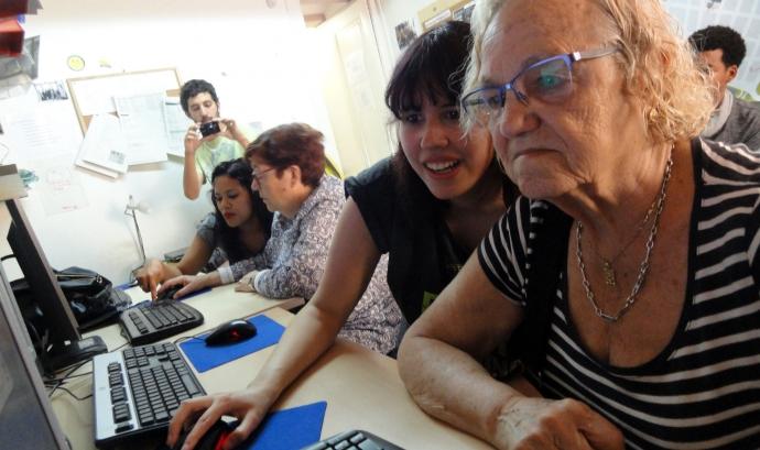 Una jove ensenya a fer servir l'ordinador a una senyora gran