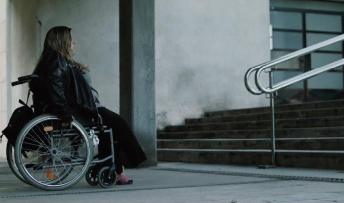 Dona amb cadira de rodes davant d'unes escales