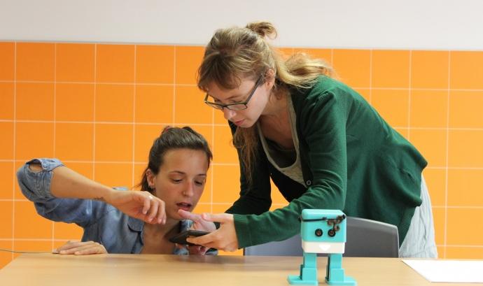 Dues dinamitzadores digitals participant en un esdeveniment de robòtica educativa