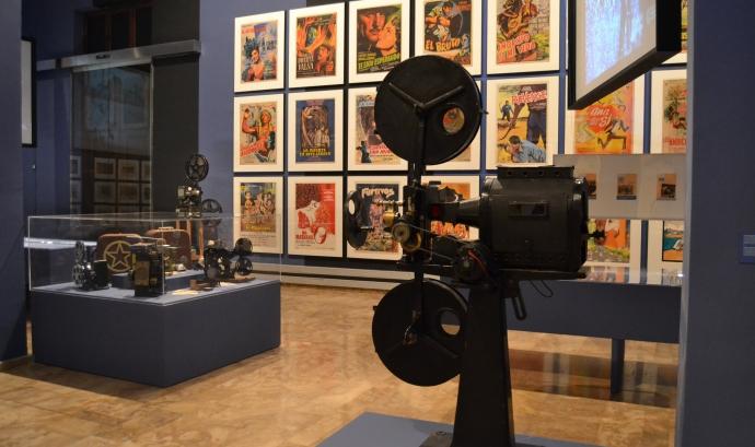 Exposició de cinema amb cartells de películes i un projector antic.