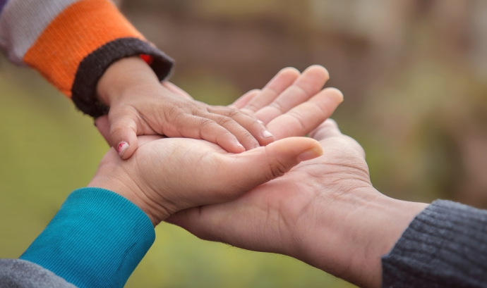 Dues mans adultes subjectant la mà d'un infant.