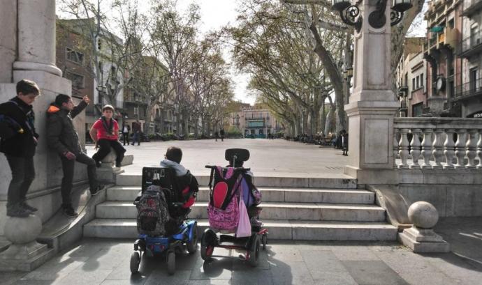 Infants escoltes i joves amb mobilitat reduïda davant l'obstacle d'unes escales.
