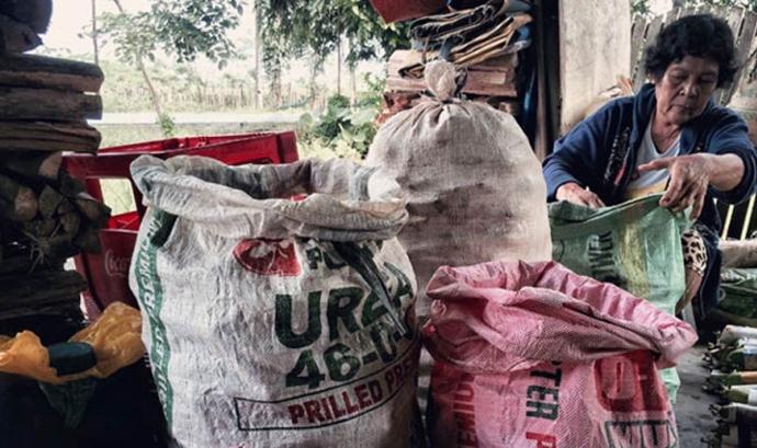 Dona indígena treballant amb sacs