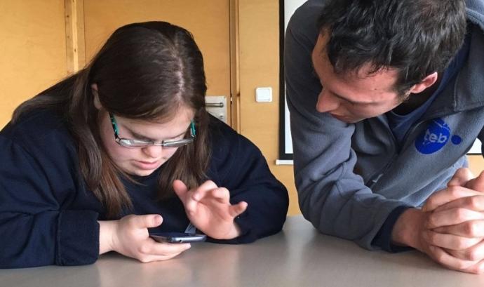 Noia amb síndrome de Down fa servir un telèfon mòbil davant d'un monitor