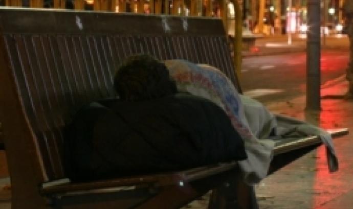 Persona dormint estirada a un banc del carrer de la ciutat de Barcelona.  Foto: Arrels Fundació