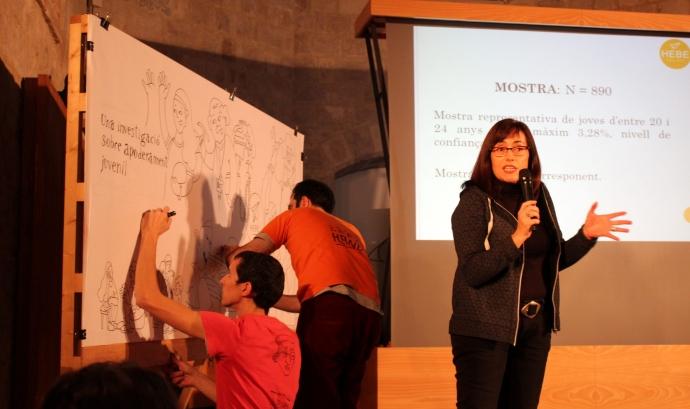 Una dona explicant del Projecte HEBE mentre dos joves il·lustren l'apoderament juvenil en un mural in-situ.