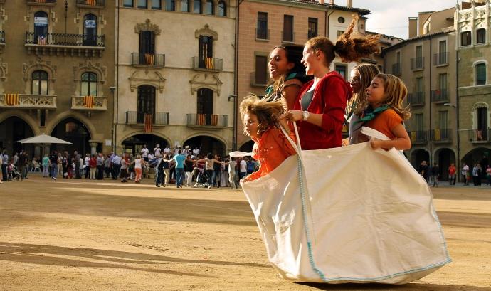 Cinc nenes fent una cursa de sacs totes dins un sac de runa