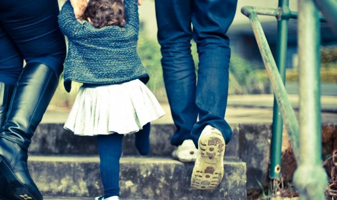 Infant de la mà de pare i mare pujant unes escales