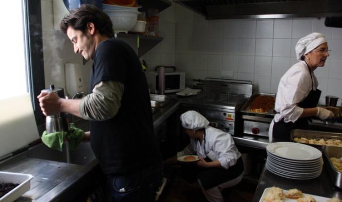 Un dels clients de La Trobada de Terrassa ajudant dues de les cuineres (ACN) Font: